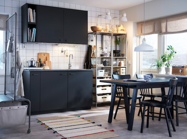 A white-walled kitchen with black cabinets, a tall metal shelving unit, and a black wood dining table with black chairs.