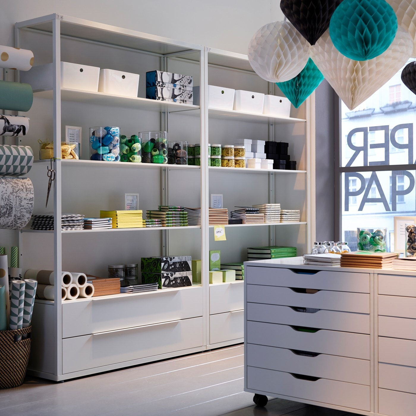 A white-walled paper shop with colourful paper lanterns, white shelving units and white ALEX drawer units on castors.