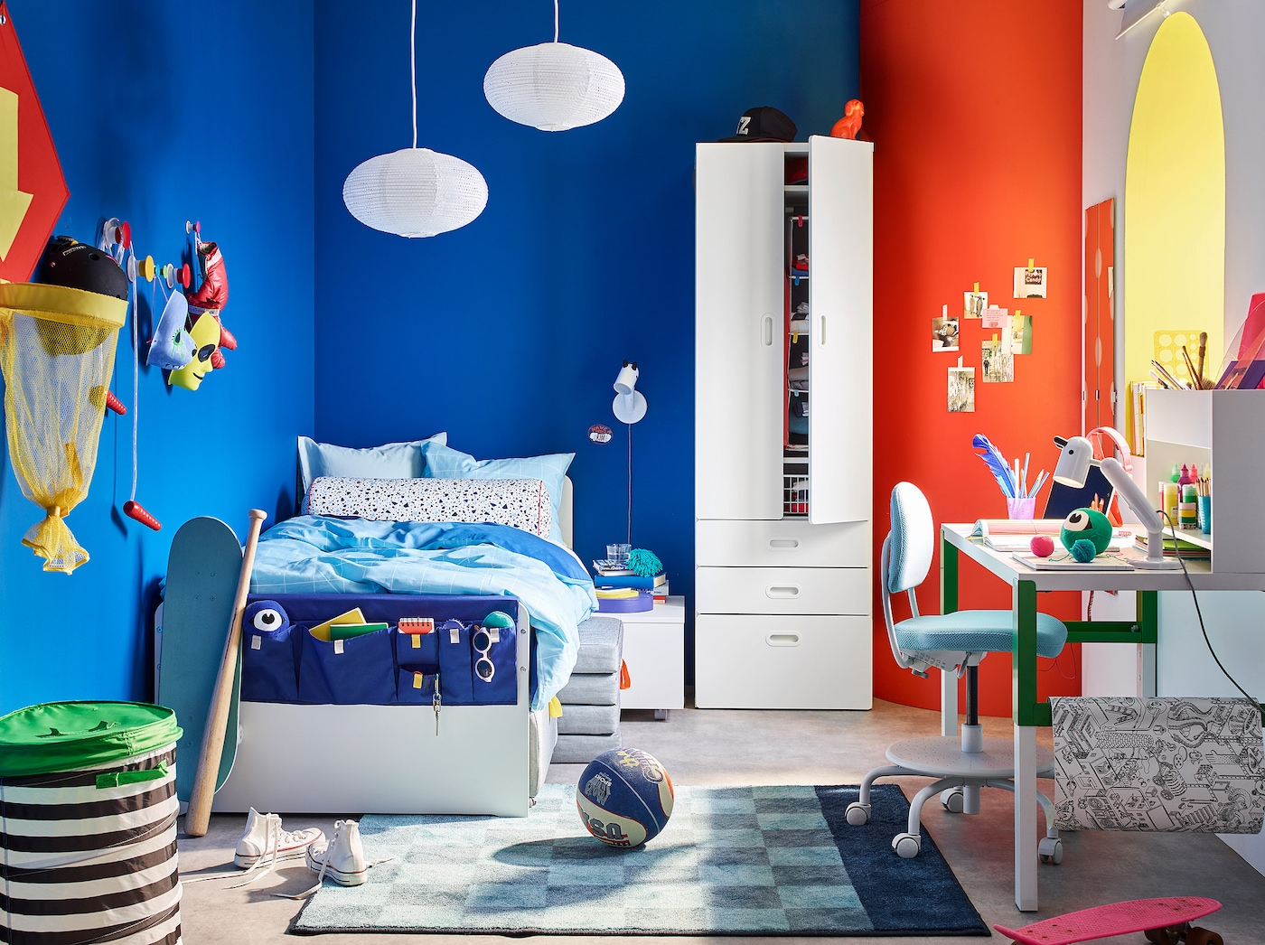 A white wardrobe and a white bed with colorful bedspreads, bright bold wall colors and a nearby desk with chair.