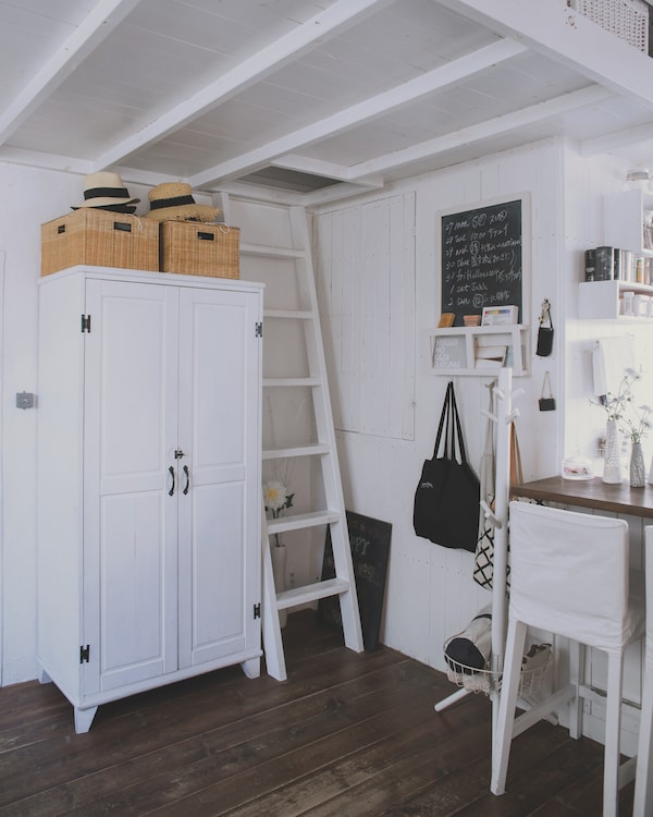 A white wardrobe in a white home with dark wood floors.