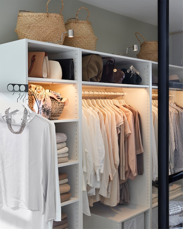 A white wardrobe, nickel-plated cabinet lighting, clothes rails and baskets in seagrass.