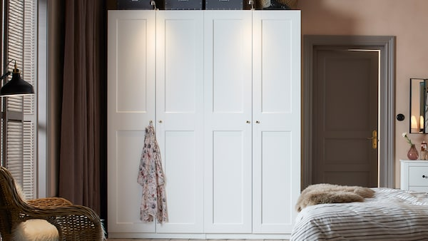 A white wardrobe unit with double doors