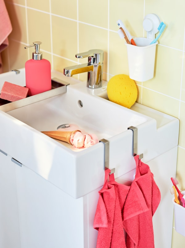 A white washbasin cabinet with accessories and towels in coral and white. An ice cream is melting in the washbasin.