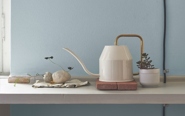 A white watering can with gold-colour handle on a shelf with pot plant and stones.