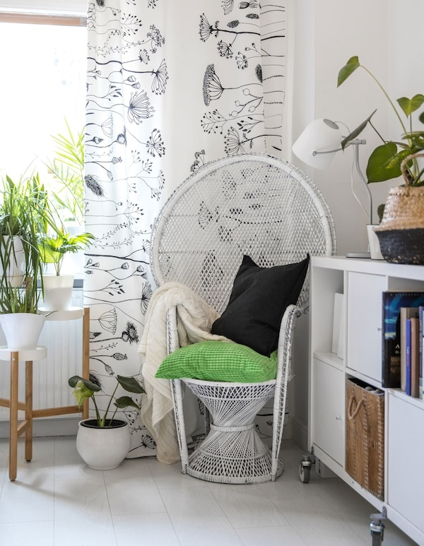 A white wicker chair in the corner of a white bedroom with green accents and plants.