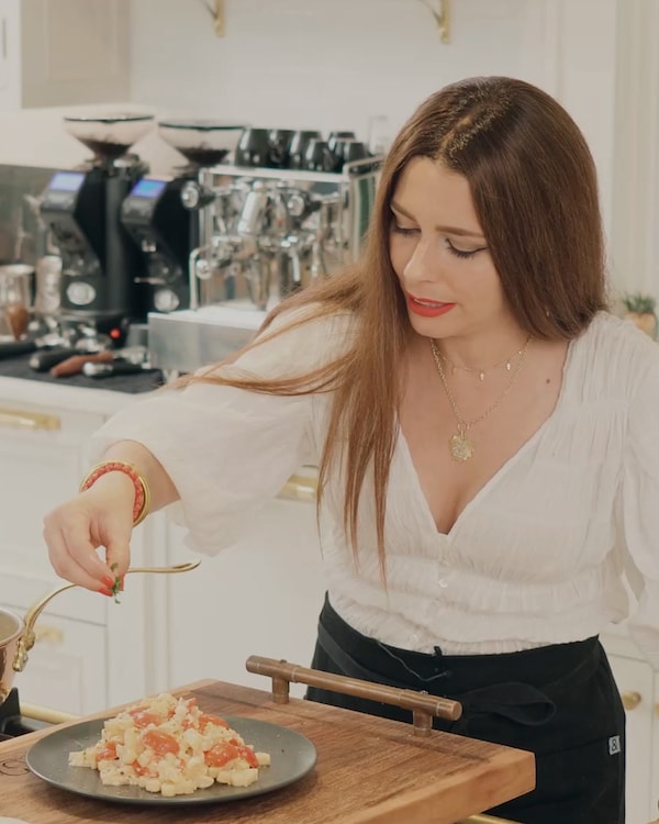 A white woman with long brown hair wearing a white blouse sprinkles a green garnish on top of a plate of freshly cooked pasta.