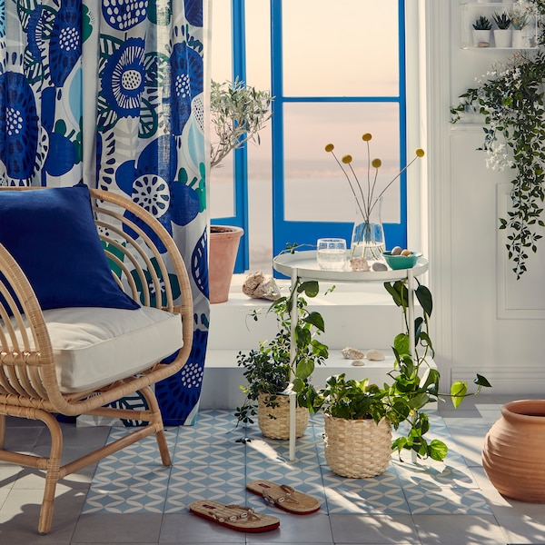 A wicker armchair wih a white side table and blue and white patterned rug.