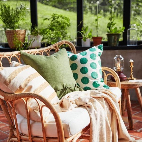 A wicker sofa with a warm olive AINA cushion, KNIPPARV cushion and ÅSATILDA polka dot cushion.