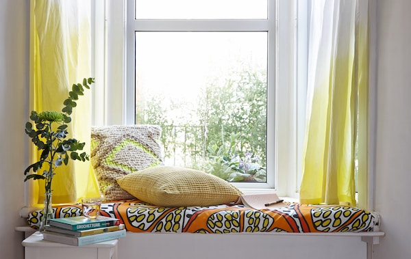 A window seat with dip-dyed curtains.