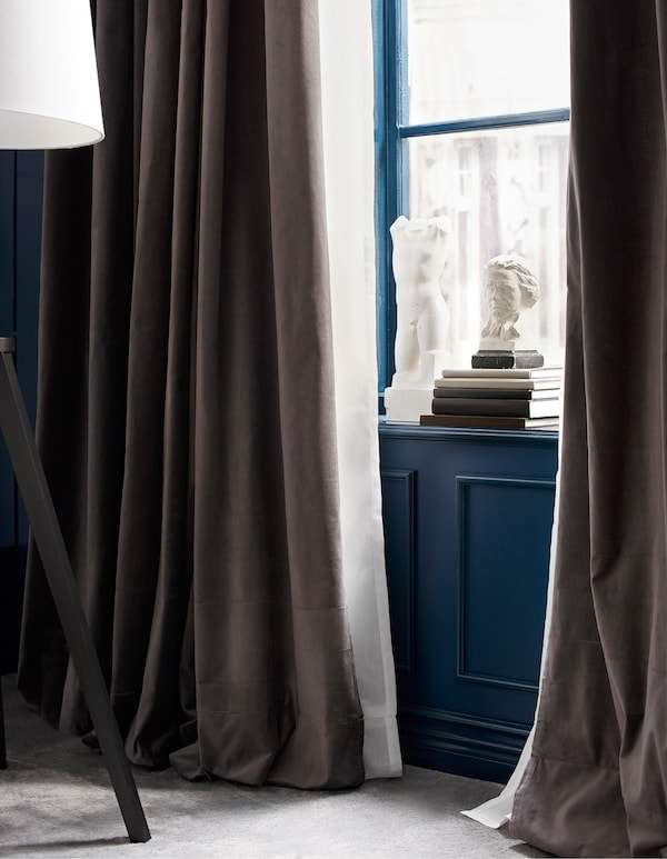 A window with two layers of curtains, one heavy brown, one light white.