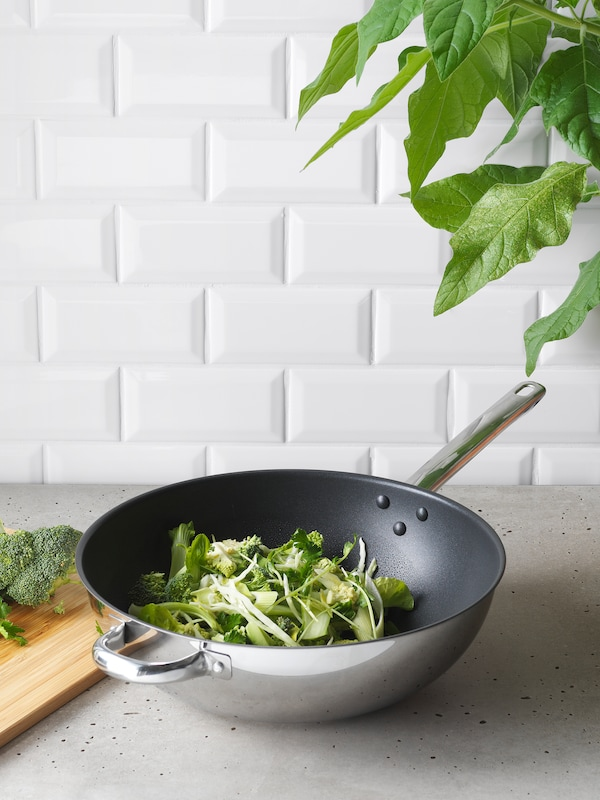 A wok containing fresh green vegetables such as broccoli stands on a gray kitchen countertop.