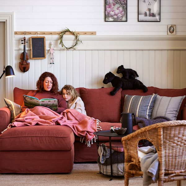 A woman and a girl are covered in a throw and read a book together on a light-red GRÖNLID three-seat sofa with chaise longue.