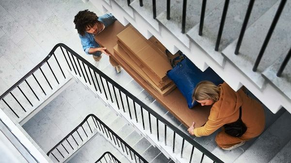 A woman and a man carry several packages of furniture up a stairwell