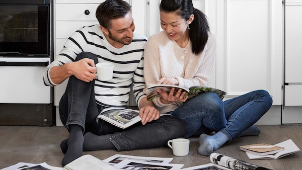 A woman and a man sit in the kitchen on the floor in front of the kitchen counter, leafing through catalogues and laughing