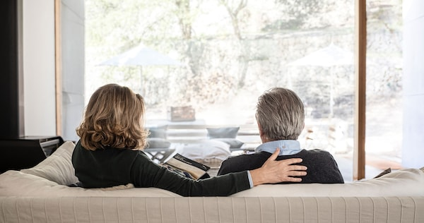 A woman and a man sitting on a sofa reading a magazine