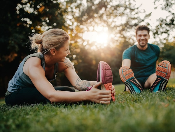 A woman and a man stretching after exercising.