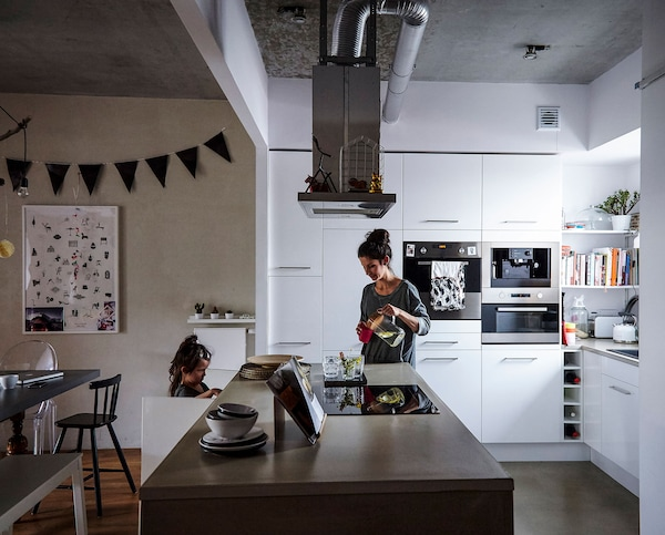 A woman and child in an integrated kitchen and living area.