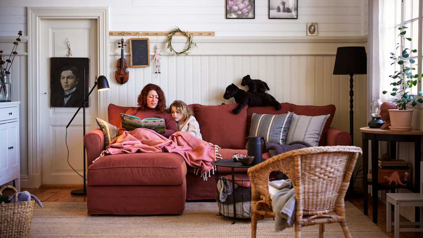 A woman and girl cosy up with a book on a light red GRÖNLID three-seater sofa with a chaise longue in a living room.