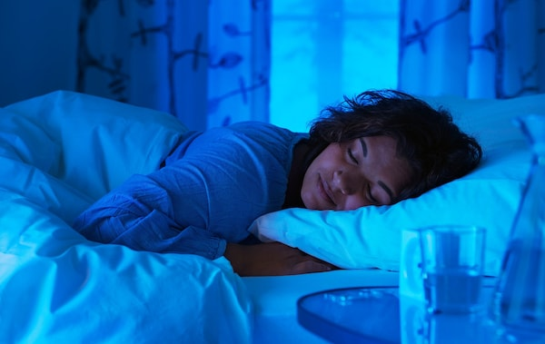 A woman asleep in a bed with curtains in the background.