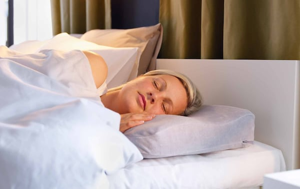 A woman asleep in bed on her side.
