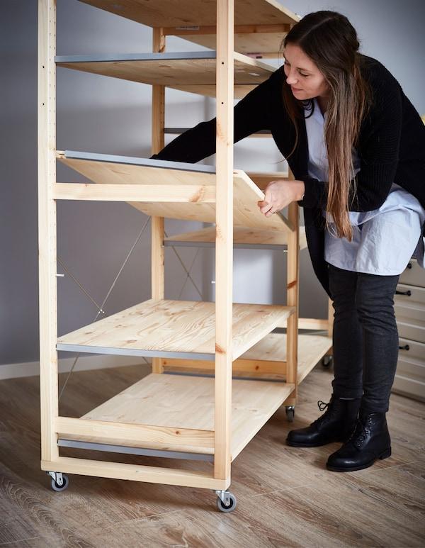 A woman assembling an IVAR shelf.