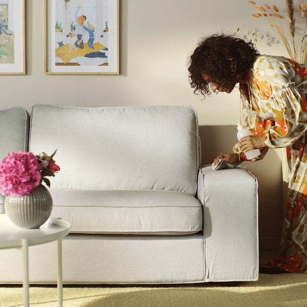 A woman cleans a light-grey sofa arm.