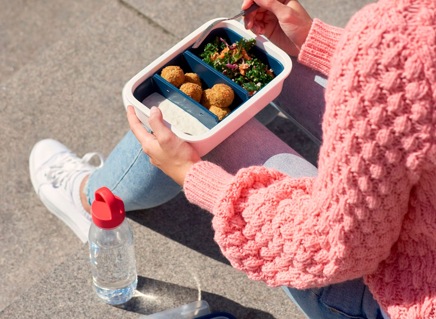 A woman eating from an IKEA plastic food container, with a transparent plastic bottle filled with water beside her.