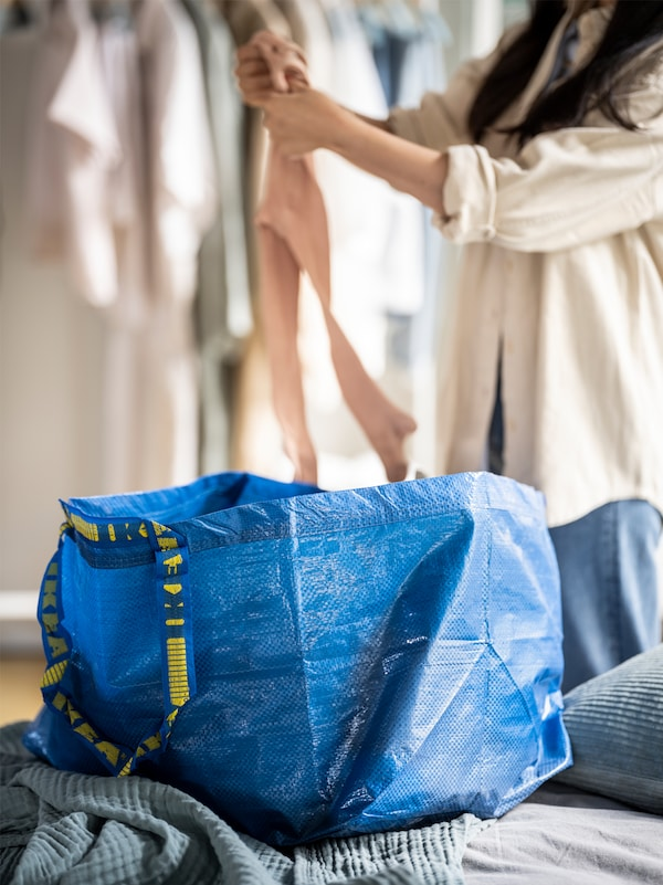 A woman folding clothes behind a bed with a big blue IKEA bag on it and clothes hanging on a rail in the background.