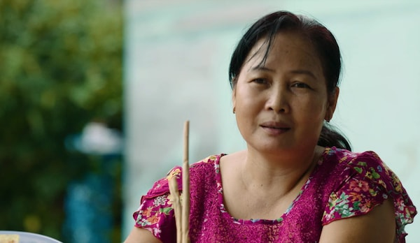 A woman from Vietnam in a pink blouse.