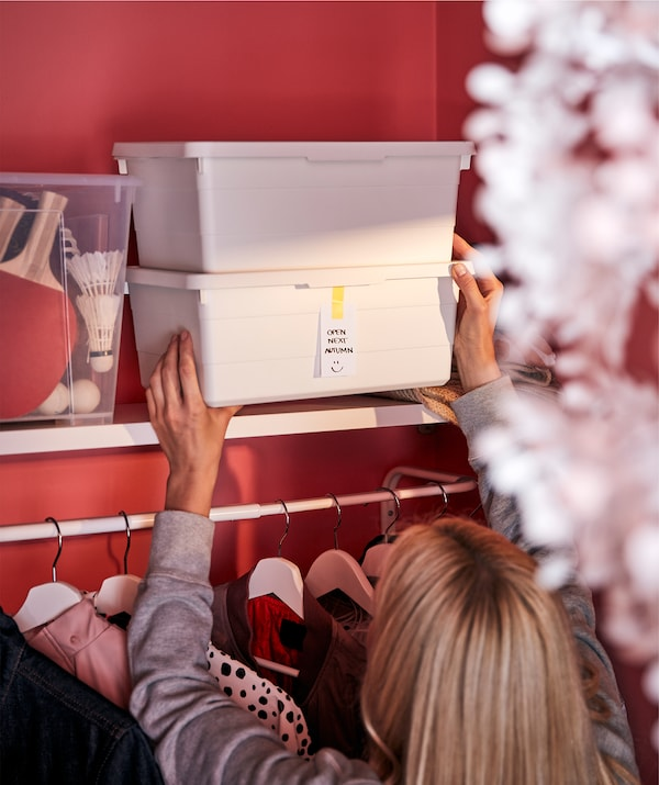 A woman handles a stack of two white SOCKERBIT boxes placed next to a transparent box on an overhead shelf in a wardrobe.