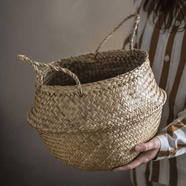 A woman holding a seagrass FLÅDIS basket against a beige background.