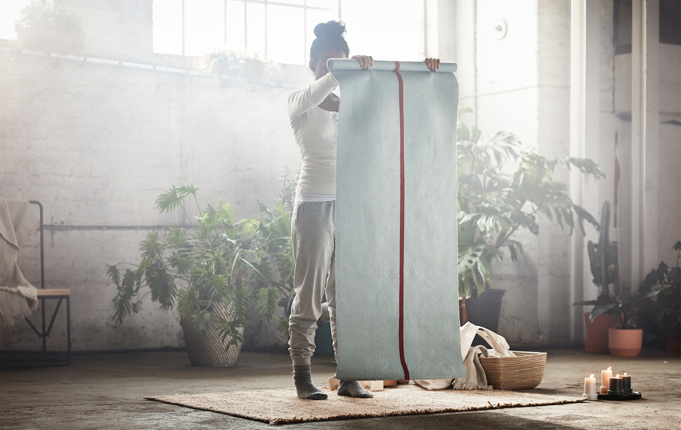 A woman holding up a yoga mat surrounded by indoor plants in a warehouse.