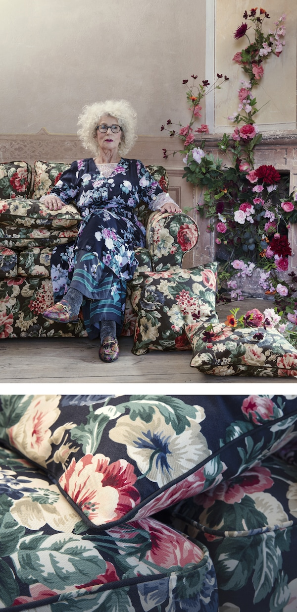 A woman in a floral dress on a floral sofa next to a fireplace dressed with flowers.