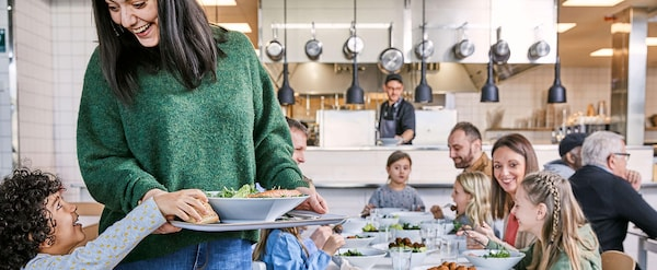 A woman in a green sweater holding a tray of food with people dining behind her in the IKEA Restaurant.