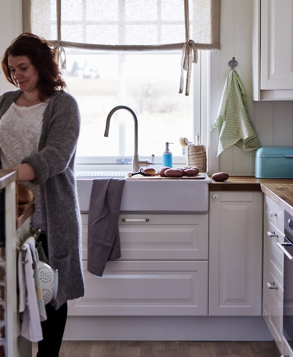 A woman in a kitchen, close to a kitchen sink.