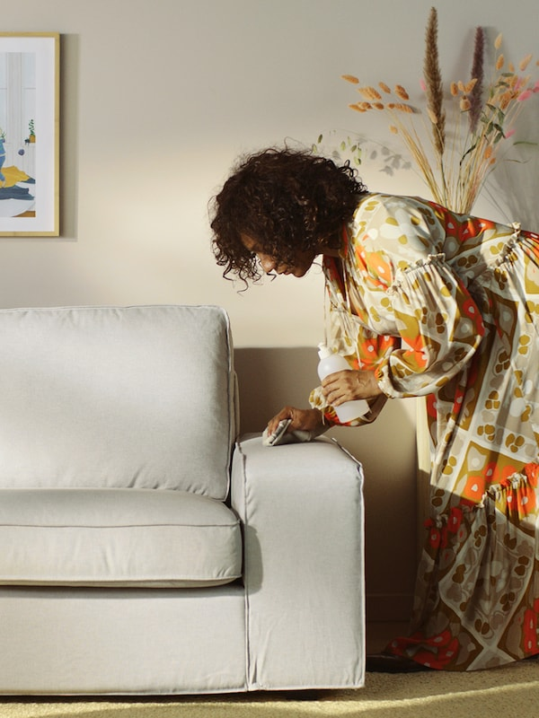 A woman in a sunny room with a bottle of cleaning fluid in one hand and a cloth in the other wiping the arm of a grey sofa.