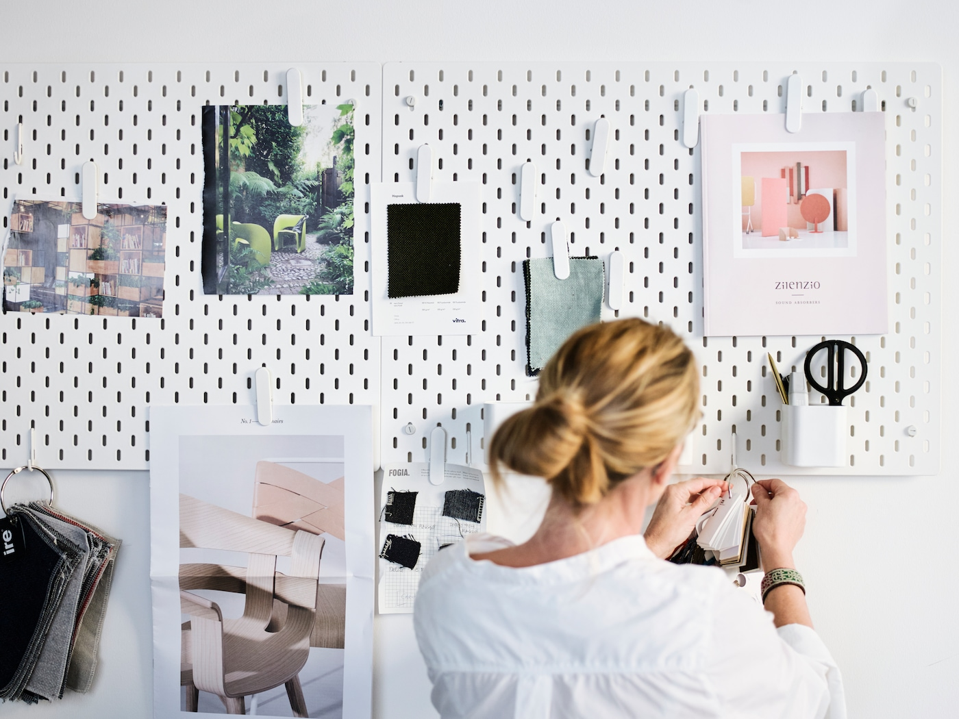 A woman in a white shirt arranging pictures on the board.