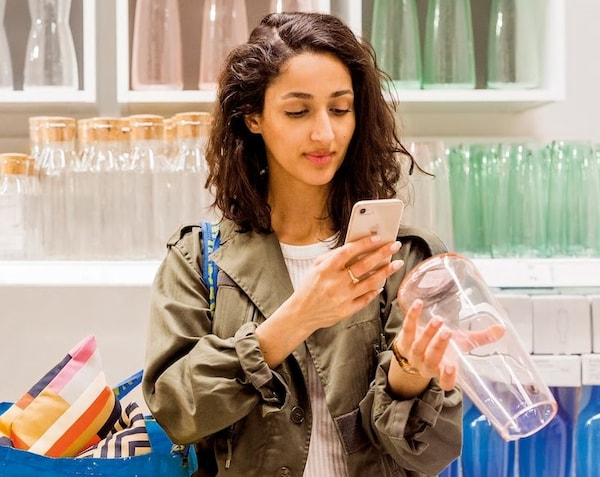 A woman in an IKEA store scanning a vase with her phone.