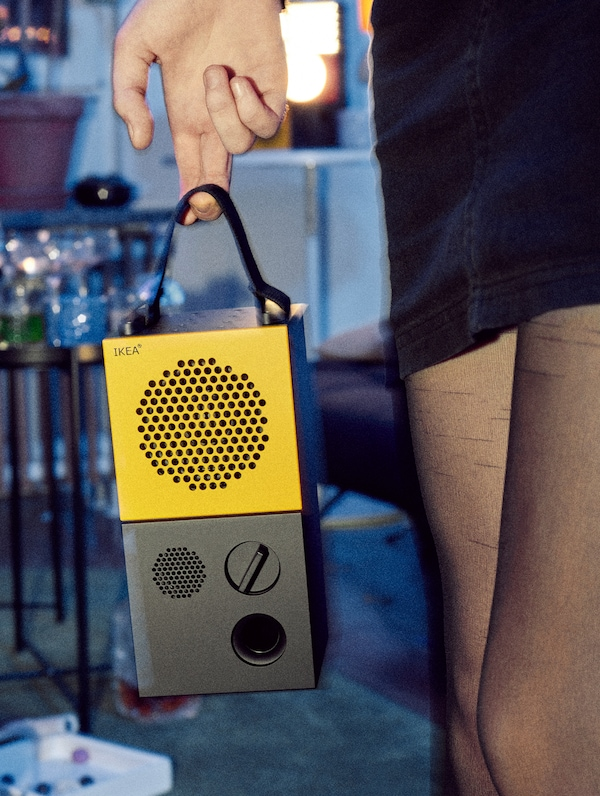 A woman in black tights and a mini skirt holding an IKEA FREKVENS portable speaker in yellow and black.