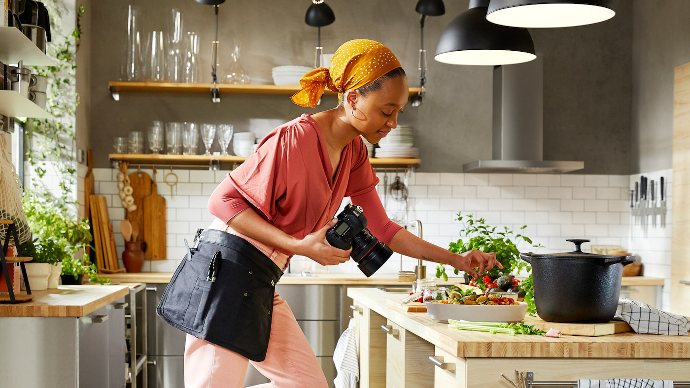 A woman in pink clothes and orange headscarf garnishes food in a kitchen as she holds a camera in the other hand.