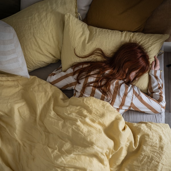 A woman in striped pyjamas sleeping in a bed made with yellow bed linen, plus brown and white extra pillows.