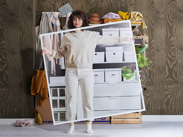 A woman in white clothes stands in front of messy shelves holding a large picture of the shelves when they've been tidied up.