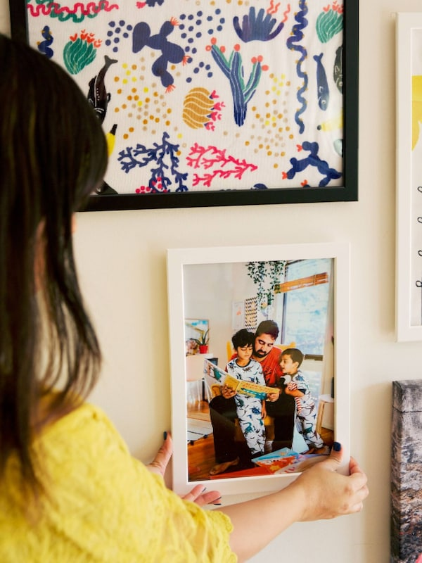A woman in yellow positioning a family photo on a gallery wall of pictures.