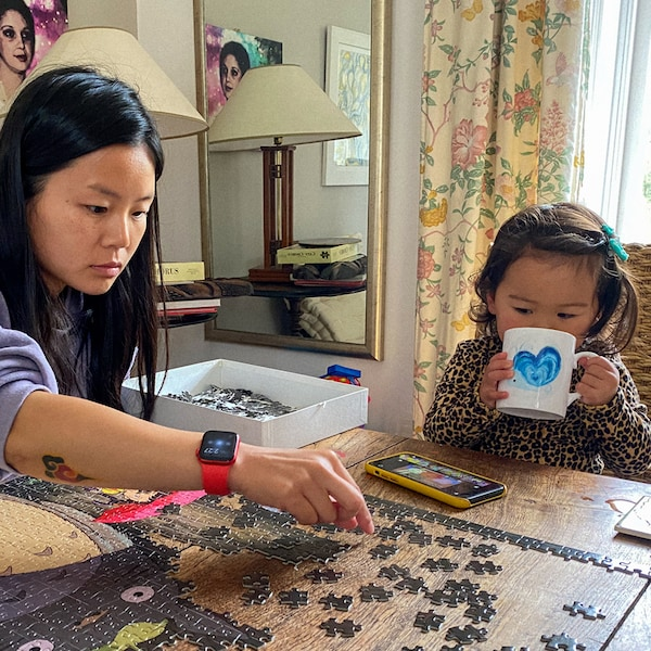 A woman is building a puzzle on a coffee table. Her daughter is sitting next to her, drinking from a mug.