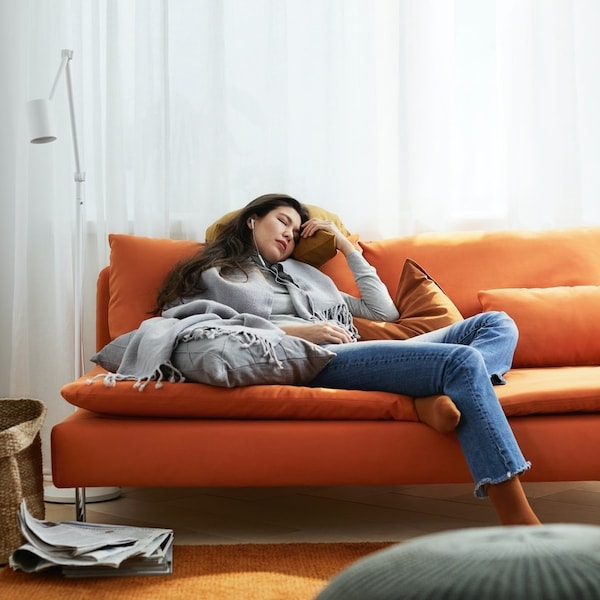 A woman is relaxing and listening to music on an orange SODERHAMN couch.