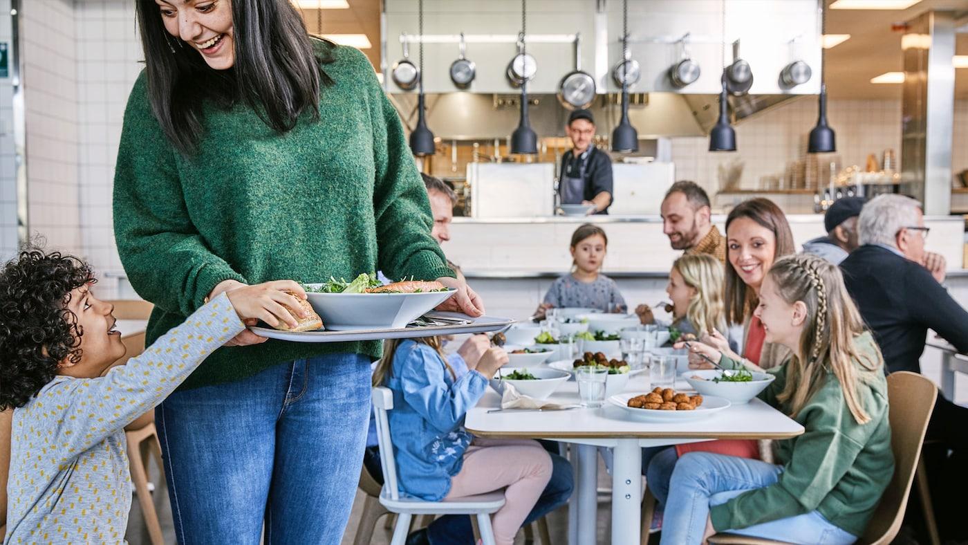 A woman is sitting at a table with her IKEA Étteremben ül egy nő két gyermekével. Fenntartható ételeket fogyasztanak.