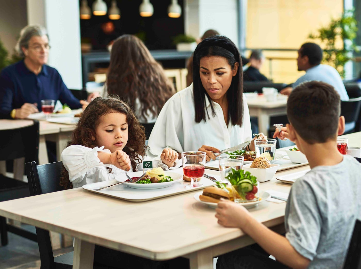 A woman is sitting at a table with her two children in an IKEA Restaurant. They are eating sustainable meals.