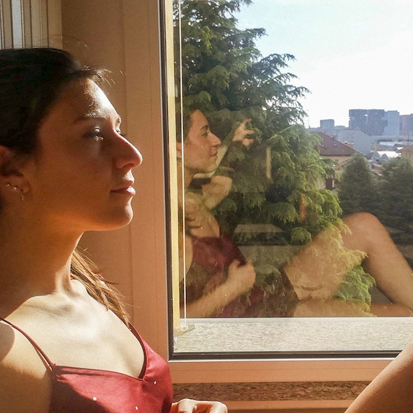 A woman is sitting on a sun-filled windowsill with her eyes closed. Her reflection is visible in the window next to her.