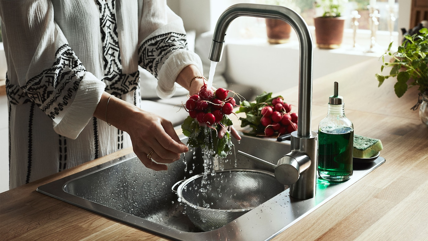 A woman is washing fruits by using ÄLMAREN kitchen tap in stainless steel color.