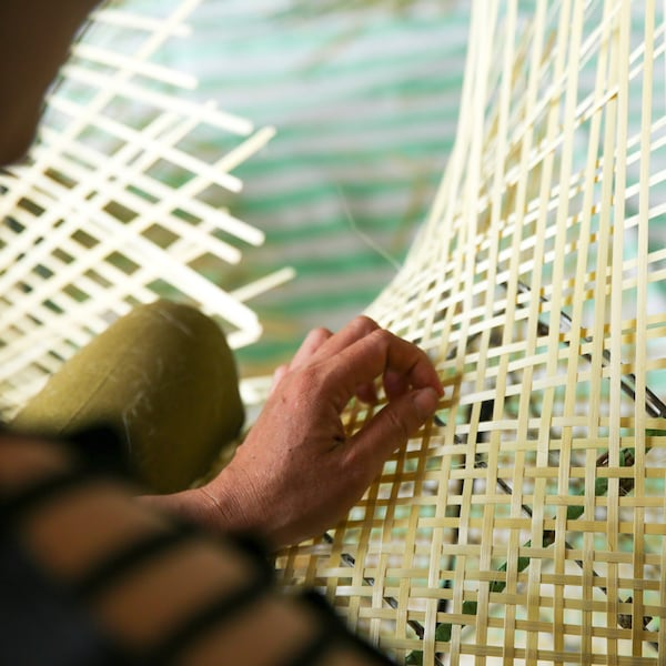 A woman is weaving bamboo with her hand to create an IKEA KNIXHULT lamp.